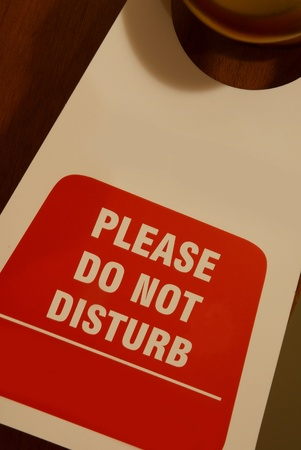 Signboard hanging on a door written  please  do not disturb photo