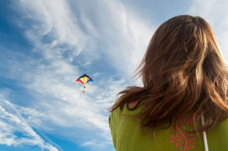 the girl starts colorful kite flying on the background of white clouds and blue sky photo