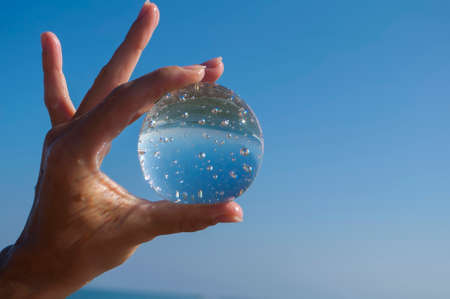 transparent crystal ball holds a womans hand on a background of blue sky