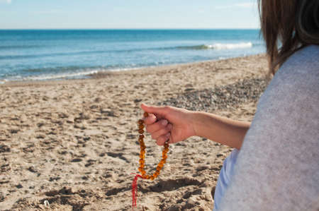 girl with beads in his hands sitting on the sea shore photo