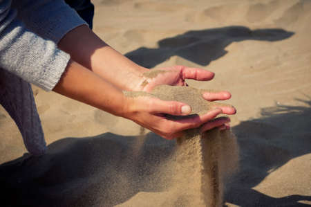 strewed: on the beach out of the girls hands strewed the sand. in the frame of the hand