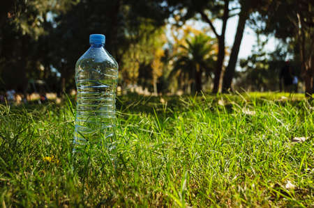 a simple bottle of mineral water stands on a background of green grass and trees in the sunshine.