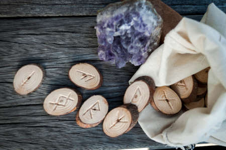 fortunetelling: wood runes handmade on an old wooden table. Esoteric subjects