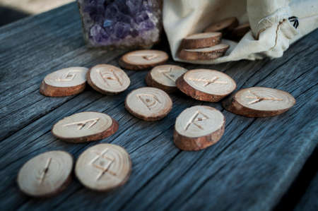 esoteric: wood runes handmade on an old wooden table. Esoteric subjects