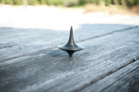 rigidity: the black spinning gyroscopet is spun on an old wooden table