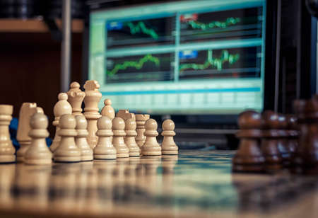 chess board: the chess pieces on the Board before the game on the background are Forex charts Stock Photo