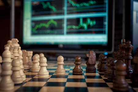 battling: the chess pieces on the Board before the game on the background are Forex charts Stock Photo