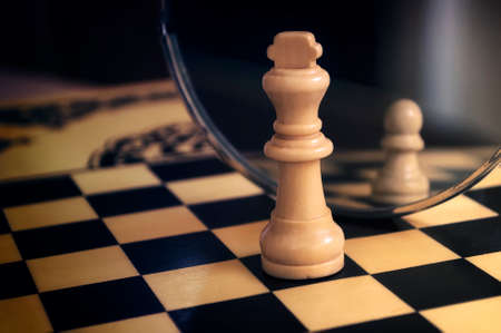 the white Queen stands before the mirror in the reflection of a white pawn chess pieces