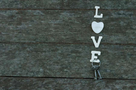 key words art: the word love has white lettering on a background of old weather-beaten wood, heart and keys