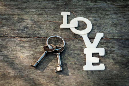 posted: posted letters the word love and the keys on an old wooden table avetrana
