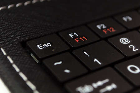 escape key: part of black keyboard laptop computer with focus on the escape button Stock Photo