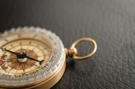 azimuth: gold plated old compass on black leather
