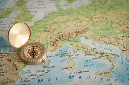 gold plated old compass lying on the map of Europe Stock Photo