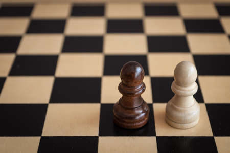pawns: two black and white pawns on a wooden chess Board Stock Photo