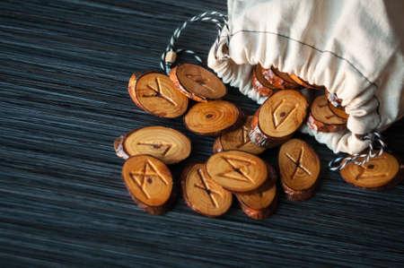 sacerdote: sobre un fondo oscuro de la bolsa de trapo derramado unas cuantas runas de madera