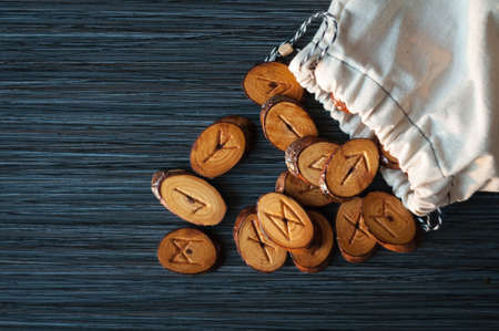 runes: on a dark background from the rag bag spilled a few wooden runes Stock Photo