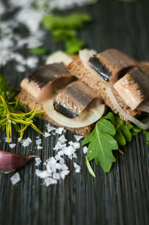 pieces of delicious herring on black bread on the table with greens