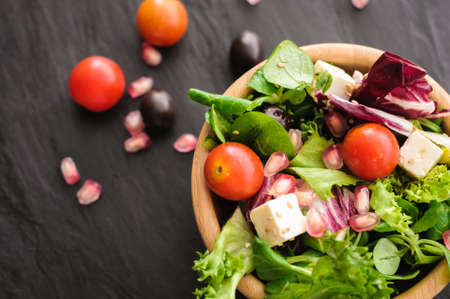vegetarian food is salad, canonigo tomatoes olives pomegranate, and feta cheese. on a black background Stock Photo