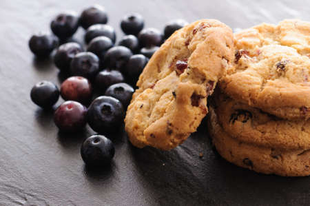 a few homemade cookies and blueberries on black background Stock Photo