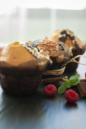 three muffin with nuts, raspberries and chocolate pieces on black background Stock Photo