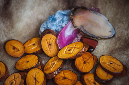 wood runes handmade fur are lying beside the crystal ball and semi-precious stones