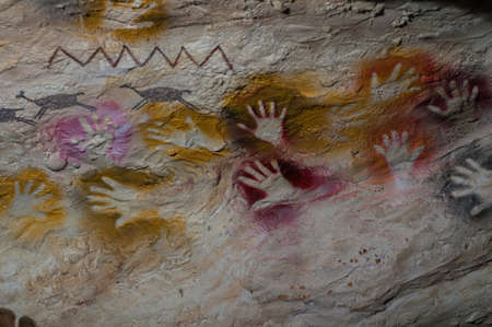 Handprints of an ancient man on the wall of a prehistoric cave .