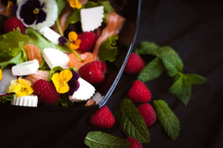 Salad with raspberry fruit, flowers, cheese, and salmon on black background Stock Photo