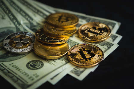 gold coins bitcoin lie on a pack of banknotes dollars