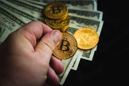 A hand hold a golden coin of bitcoin on a background of dollar bills are coins bitcoin Stock Photo