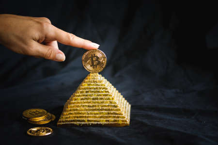 A finger holds a gold coin bitcoin on top of the pyramid Stock Photo