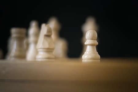 plusieurs pièces d'échecs blanches sur un échiquier avec un pion au centre Banque d'images