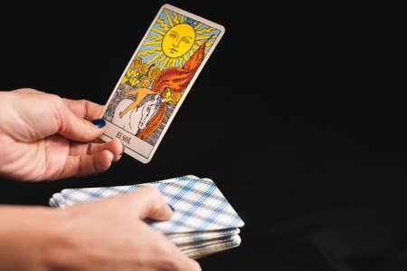 Cartes de tarot senior Arcana dans les mains d'une femme sur fond noir Banque d'images