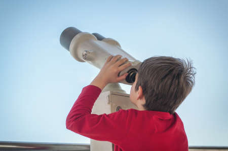 the boy watches the tourist telescope on