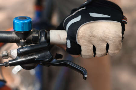 close-up of a mans gloved hand on the handlebars of a mountain bike