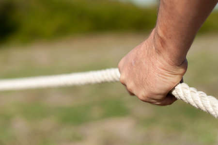 strong male hands firmly hold or pull the rope outdoor