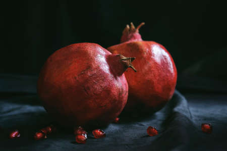 a few ripe whole pomegranates with a few berries on a dark background Stok Fotoğraf - 133040735