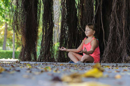 Little girl meditates under a tree