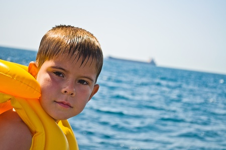 floatable: Boy in life jacket, standing in the background of the sea Stock Photo