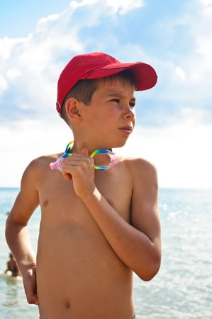 A boy in a baseball cap, standingagainst the backdrop of the sea photo