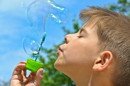 A little boy blows bubbles. Background sky. Stock Photo - 9571673