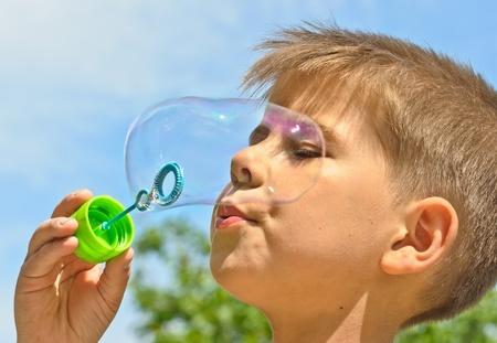 A little boy blows bubbles. Background sky. photo