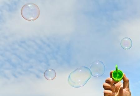 A little boy blows bubbles. Background sky.