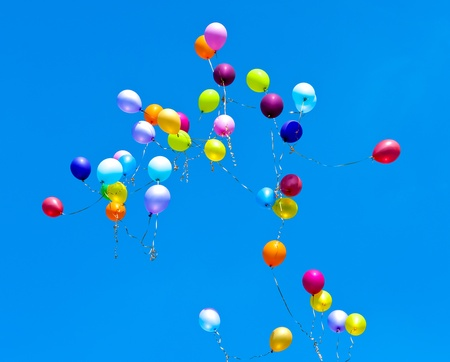 Many balloons fly into the blue sky Stock Photo
