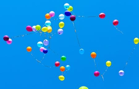 Many balloons fly into the blue sky Archivio Fotografico