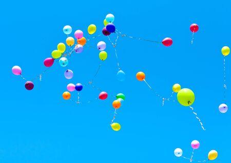 Molti palloncini volano in cielo blu Archivio Fotografico