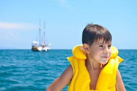 The boy in the swimming vest. In the background is a ship Stock Photo