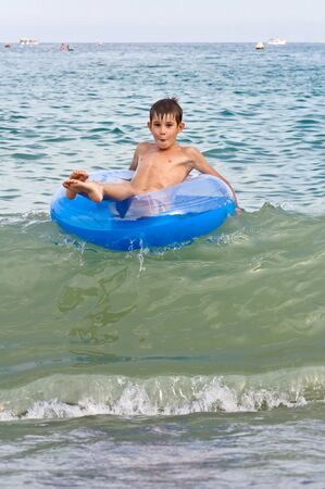 Boy with inflatable rides around on the waves. summer sea photo