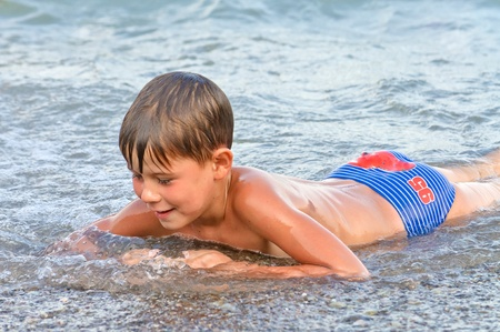 boy body: Boy playing in the surf. summer sea