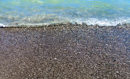 Sea surf on the rocks falling pebble beach