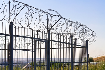 Fence of barbed wire. Against the blue sky photo